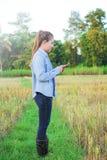 Rolnik używa cyfrowego telefon w kultywującym ryżu polu Obrazy Royalty Free