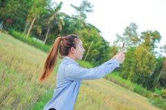 Rolnik używa cyfrowego telefon w kultywującym ryżu polu Zdjęcie Royalty Free