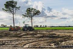 Rolnik w ciągnikowej narządzanie ziemi z seedbed kultywatorem Zmierzch fotografia royalty free