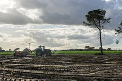 Rolnik w ciągnikowej narządzanie ziemi z seedbed kultywatorem Zmierzch fotografia stock