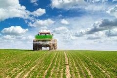 Rolnik w ciągnikowym nawozowym pszenicznym polu przy wiosną z npk zdjęcie stock