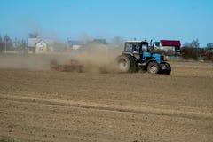 Rolnik w ciągnikowej narządzanie ziemi z seedbed kultywatorem jako część pre siać aktywność w wczesnym wiosna sezonie rolniczy zdjęcia stock