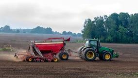 Rolnik w jesieni taktuje pola z ciągnikiem i bogaci one z kopalnymi użyźniaczami obraz royalty free
