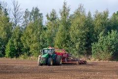 Rolnik w jesieni taktuje pola z ciągnikiem i bogaci one z kopalnymi użyźniaczami fotografia royalty free