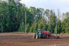 Rolnik w jesieni taktuje pola z ciągnikiem i bogaci one z kopalnymi użyźniaczami zdjęcie stock