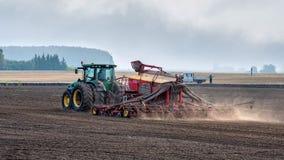 Rolnik w jesieni taktuje pola z ciągnikiem i bogaci one z kopalnymi użyźniaczami zdjęcia stock