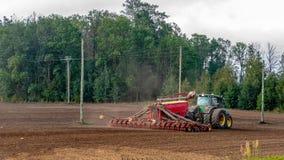 Rolnik w jesieni taktuje pola z ciągnikiem i bogaci one z kopalnymi użyźniaczami obrazy royalty free