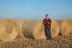 Rolnik w pszenicznym polu po żniwa z staczającą się słomą w beli zdjęcie royalty free