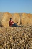 Rolnik w pszenicznym polu po żniwa z staczającą się słomą w beli obraz stock