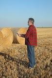 Rolnik w pszenicznym polu po żniwa z staczającą się słomą w beli obrazy royalty free