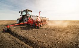 Rolnik z ciągnikowego obsiewania wysiewnymi uprawami przy rolniczym polem zdjęcie royalty free