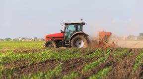 Rolnik z ciągnikowym obsiewaniem - siać uprawy przy rolniczym polem obraz stock