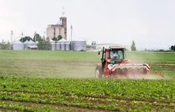 Rolnik z ciągnikowymi obsiewanie soj uprawami przy rolniczym polem zdjęcie stock