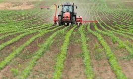 Rolnik z ciągnikowymi obsiewanie soj uprawami przy rolniczym polem obrazy stock