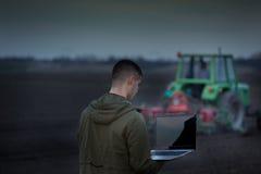 Rolnik z laptopem i ciągnikiem obraz stock