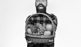 Rolnik z z podnieceniem twarzą przedstawia jabłka, winogrona i cranberries, zdjęcia stock