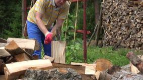 Rolnika rozszczepiony ciężki drewno z cioską w kraju blisko woodshed 4K zdjęcie wideo
