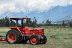Rolny ciągnik w siana polu przeciw Skalistym górom obrazy stock