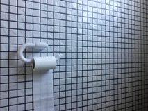 Rolo branco do papel higiênico contra uma parede preto e branco do mosaico Imagens de Stock Royalty Free
