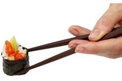 Rolo com os salmões nos chopsticks (trajeto isolado) Fotos de Stock Royalty Free
