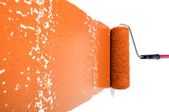 Rolo com pintura alaranjada na parede branca Fotos de Stock