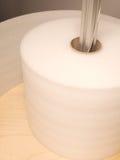Rolo da espuma branca do empacotamento industrial em um distribuidor do carretel Fotografia de Stock