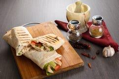 Rolo da galinha de Shaurma em um pão árabe com legumes frescos e composição do molho de creme no fundo de madeira Fotos de Stock
