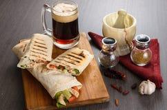 Rolo da galinha de Shaurma em um pão árabe com legumes frescos e composição do molho de creme no fundo de madeira Foto de Stock