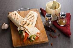 Rolo da galinha de Shaurma em um pão árabe com legumes frescos e composição do molho de creme no fundo de madeira Imagem de Stock