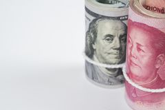 Rolo de cem notas de dólar dos E.U. e das cédulas chinesas w do yuan Fotos de Stock Royalty Free