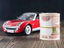 Rolo de cinco milésimas notas dos rublos no contexto de toycar imagens de stock