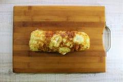 Rolo de ovos fritos delicioso em uma placa de corte de madeira imagem de stock royalty free