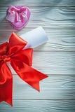 Rolo de papel com a caixa vermelha do presente do metal da curva no holida da placa de madeira Imagem de Stock