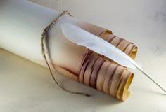 Rolo de papel velho, amarrado com uma corda, e uma pena branca fotografia de stock royalty free