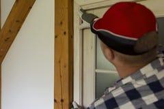 Rolo de pintura com amostras da pintura Um trabalhador manual que instala uma laje de madeira de fechamento para imagens de stock