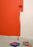 Rolo de pintura vermelho pela parede Foto de Stock