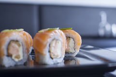 Rolo de sushi com queijo creme e os salmões fritados Coberto com s cru Fotos de Stock Royalty Free