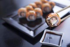 Rolo de sushi com queijo creme e os salmões fritados Coberto com s cru Fotografia de Stock
