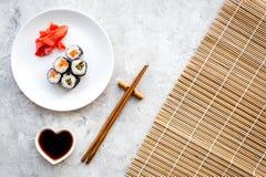 Rolo de sushi com salmões e abacate na placa com molho de soja, hashi, wasabi na esteira na opinião superior do fundo de pedra ci fotos de stock