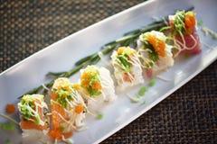 Rolo de sushi com a vara do caranguejo na placa branca, estilo japonês da vista superior do alimento Foto de Stock