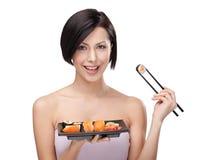 Rolo de sushi de sorriso da terra arrendada da mulher Fotografia de Stock Royalty Free