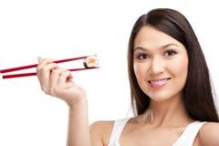 Rolo de sushi de sorriso da terra arrendada da mulher com chopsticks Imagens de Stock Royalty Free
