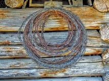 Rolo do arame farpado que pendura no close up da parede da cabana rústica de madeira Fotografia de Stock