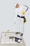 Rolo do assoalho de telhas da primeira demão de pintura do trabalhador Imagens de Stock Royalty Free
