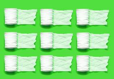 Rolo do papel higiênico branco em um fundo verde com espaço vazio imagem de stock