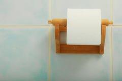 Rolo do papel higiênico que pendura no banheiro na parede fotografia de stock royalty free