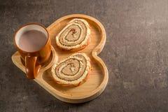 Rolo doce com creme com chocolate de leite quente em uma bandeja coração-dada forma de madeira imagem de stock royalty free