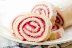 Rolo doce fresco com doce de morango e açúcar pulverizado em uma placa e em uma toalha branca Foto de Stock