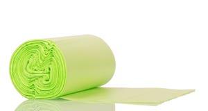 Rolo dos sacos de lixo plásticos verdes isolados no fundo branco fotografia de stock royalty free