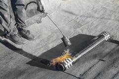 Rolo que telha a instalação com o maçarico do propano durante obras foto de stock